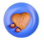 Heart-shaped cookie with hazelnut on saucer isolated on white — Stock Photo