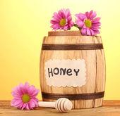 Süßer honig im fass mit drizzler auf holztisch auf gelbem grund — Stockfoto