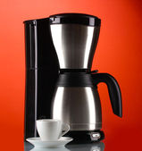 Coffee maker with white cup on red background — Stock Photo