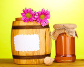 Dulce miel en tarro y el barril con drizzler en mesa de madera sobre fondo verde — Foto de Stock