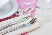 Table setting with fork, knife, plates, beads and napkin — Stock Photo