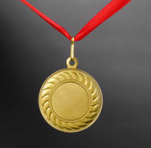Gold medal on grey background — Stock Photo