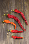 Dried chili peppers on wooden background — Stock Photo
