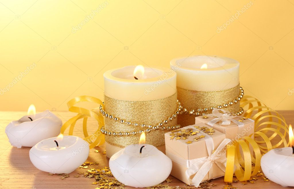 Beautiful candles, gifts and decor on wooden table on yellow background  Stock Photo #10895551