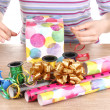 Stock Photo: Wrapping presents surrounded by paper, ribbon and bows