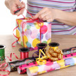 Wrapping presents surrounded by paper, ribbon and bows — Stock Photo