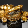Beautiful golden bracelets, rings and jewelry on grey background - Lizenzfreies Foto