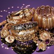 Beautiful golden jewelry on purple background - Lizenzfreies Foto