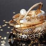 Beautiful golden bracelets on grey background — Stock Photo #10922368