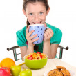 Little beautiful girl have a breakfast on white background — Stock Photo