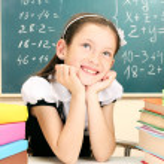 Little schoolgirl and books in classroom near blackboard — Stock Photo