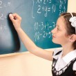 Beautiful little girl writing on classroom board — Stock Photo #10922550