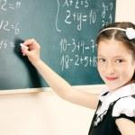 Beautiful little girl writing on classroom board — Stock Photo #10922565