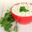 Cottage cheese with parsley and dill in red bowl on white wooden table close-up — Stock Photo #10922910