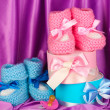 Pink and blue baby boots, pacifier and gifts on silk background — Stock Photo #10922990