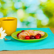Croissant with cherries and coffee on wooden table on green background — Stock Photo