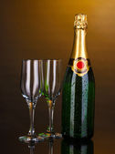 Bottle of champagne and goblets on brown background — Stock Photo
