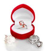 Zilveren ring met rode, roze en duidelijke kristallen in rode fluwelen doos en sommige zilveren ringen geïsoleerd op wit — Stockfoto