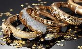 Hermosas pulseras de oro sobre fondo gris — Foto de Stock