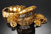 Güzel altın bilezik, yüzük ve gri arka plan üzerinde mücevher — Stok fotoğraf