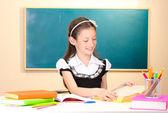 Little schoolchild in classroom write in notebook blackboard — Stock Photo