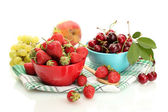 Ripe strawberries and cherry berries in bowls, grapes and apple isolated on white — Stock Photo