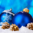 Beautiful blue Christmas balls and cones in snow on blue background — Foto Stock