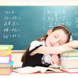 Little schoolgirl sleep in classroom near blackboard — Stockfoto