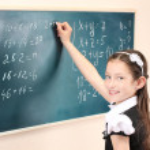 Beautiful little girl writing on classroom board — Stock Photo #10941271