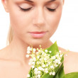 Beautiful young woman with a bouquet of lilies of the valley on white background close-up — Stock Photo #10941278