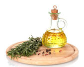 Oil in a bottle and fresh rosemaryon wooden board isolated on white — Stock Photo