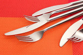 Forks and knives on a red tablecloth — Stock Photo