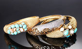Krásné zlaté náramky na šedém pozadí — Stock fotografie