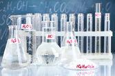 Tubos de ensaio com vários ácidos e outros produtos químicos sobre o fundo do quadro-negro — Foto Stock