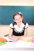 Little schoolchild in classroom write in notebook — Stock Photo