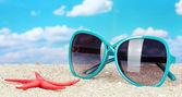 Elegant women's sunglasses with starfish at the beach — Stock Photo