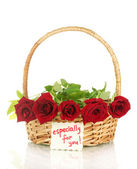 Basket with roses and a note isolated on white background close-up — Stock Photo