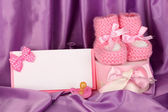 Pink baby boots, pacifierd, postcard and gifts on silk background — Stock Photo