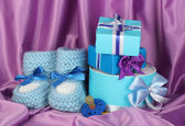 Blue baby boots, pacifier, gifts on silk background — Stock Photo