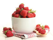 Sweet ripe strawberries in bowl on white wooden table — Stock Photo