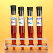 Test-tubes with blood on wooden table on yellow background — Stok fotoğraf