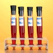 Test-tubes with blood on wooden table on yellow background — 图库照片