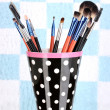 Makeup brushes in a black polka-dot cup on colorful background — Stok fotoğraf
