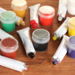 Tubes with colorful watercolors and jars with gouache on wooden table close-up — Foto de Stock