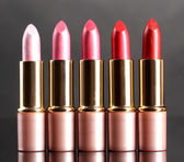 Beautiful lipsticks on gray background — Stock Photo