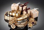 Beaux bijoux d'or et cadeaux sur fond gris — Photo