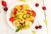 čerstvé ovoce salát na desku a bobule na bílý dřevěný stůl — Stock fotografie