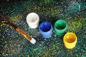 Frascos com guache colorido e escova em fundo preto, salpicada com close-up pintura colorida — Foto Stock
