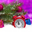 Green Christmas tree with toy and clock in the snow on purple — Stock Photo #10985361