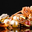 Various gold jewellery on black — Stock Photo